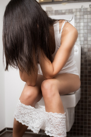 is embarrassed: Young woman using the toilet sitting on the bowl with her head in her hands and long brown hair covering her face with her lacy panties around her legs