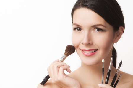Beautiful naked young woman with an array of different cosmetic brushes held fanned out in her hand smiling at the camera photo