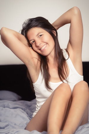 rejuvenated: Healthy woman refreshed after a good nights sleep stretching in bed and smiling at the camera in pleasure and satisfaction Stock Photo