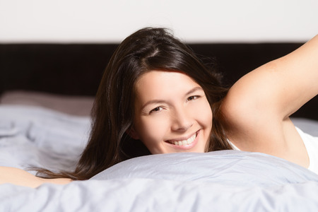 refreshed: Healthy woman refreshed after a good nights sleep stretching in bed and smiling at the camera in pleasure and satisfaction Stock Photo