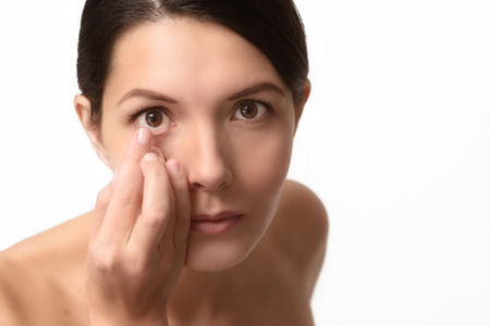 consumable: Woman about to place a disposable plastic contact lens in her eye to correct her vision has it balanced on the end of her finger in front of her face with focus to the lens