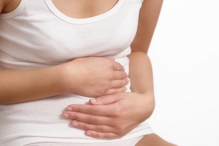 Frau mit akuten Bauchschmerzen umklammerte ihren Bauch mit den Händen, als sie wird durch die laufenden Krämpfe, Oberkörper Blick auf ihre Hände und Bauch getrennt auf Weiß betonte,
