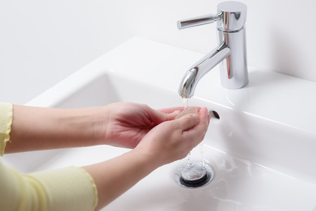 handbasin: Woman washing her hands with soap under running water from a stainless steel tap on a white ceramic handbasin