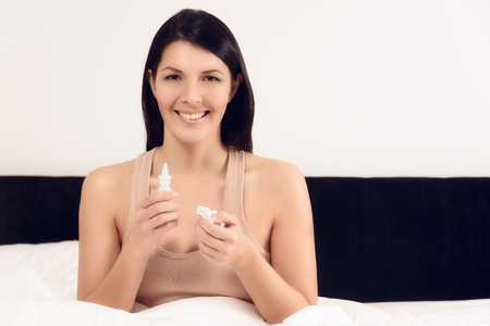 nose drops: Young woman with a bottle of inhalant or nose drops sitting in bed with a happy smile