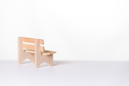 airy: Small simple rustic vacant wooden bench placed to the side in an airy bright white minimalist room with copyspace Stock Photo
