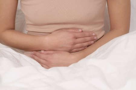 hemorragias: Mujer con sus dolores menstruales mensuales agarrándose el estómago con las manos Foto de archivo