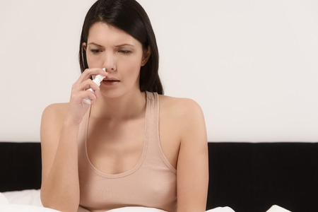 nasal drops: Young woman inhaling nose drops to relieve nasal congestion caused by a cold or an allergy resulting in hay fever Stock Photo