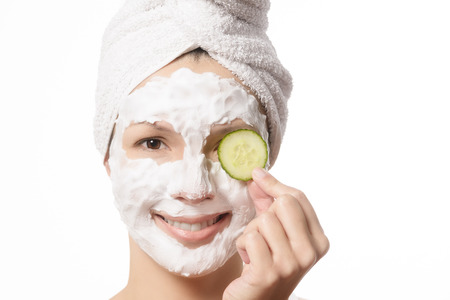 hair tied: Smiling woman with her hair tied up in a white towel and a deep cleansing nourishing face mask