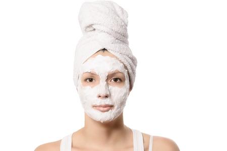 cabelo amarrado: Mulher s�ria com seu cabelo amarrado em uma toalha branca e uma m�scara facial nutritiva limpeza profunda aplicada a ela, beleza e conceito do skincare