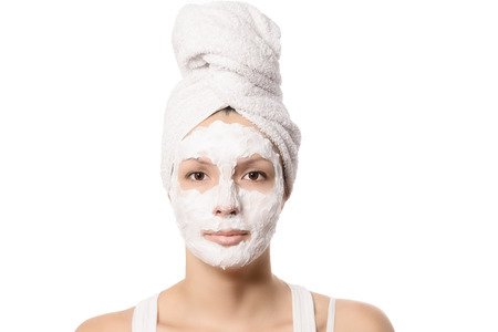 Serious woman with her hair tied up in a white towel and a deep cleansing nourishing face mask applied to her, beauty and skincare concept Фото со стока
