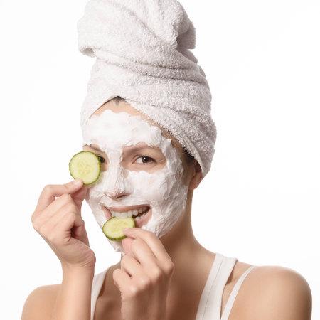 하얀 수건 및 그녀의 피부는 아름다움과 스킨 케어 개념에서 그녀의 눈에 오이의 상쾌한 조각을 들고에 적용되는 딥 클렌징 영양 얼굴 마스크에 묶여
