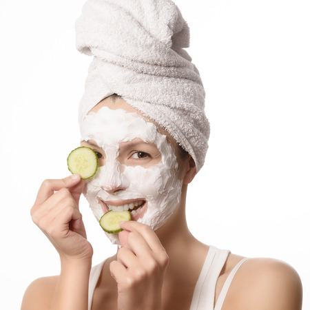 Smiling woman with her hair tied up in a white towel and a deep cleansing nourishing face mask applied to her skin holding a refreshing slice of cucumber to her eye in a beauty and skincare concept