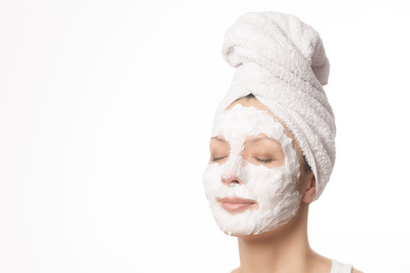 hair tied: Relaxed woman with her hair tied up in a white towel and a deep cleansing nourishing face mask applied to her face, beauty and skincare concept