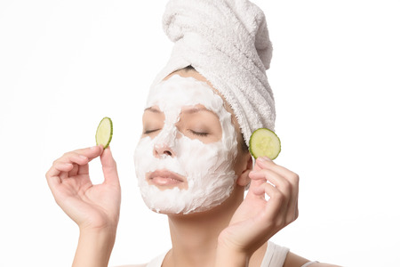 eye mask: Smiling woman with her hair tied up in a white towel and a deep cleansing nourishing face mask applied to her skin holding a refreshing slice of cucumber to her eye in a beauty and skincare concept