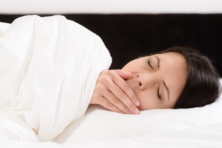 Tired attractive young woman lying in bed yawning with her hand to her mouth and eyes closed as she prepares to go into a refreshing sleep to ease her fatigue Stock Photo