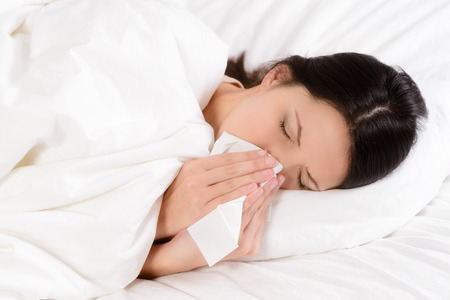 hayfever: Sick young woman lying in her clean white bed blowing her nose on a tissue conceptual of healthcare and seasonal flu and chills, rhinitis or an allergic reaction in hayfever
