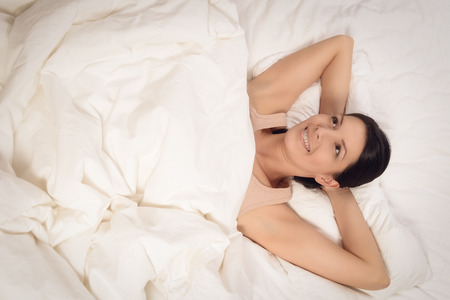 rejuvenated: Smiling healthy rejuvenated young woman snuggling down between her pillows in bed giving the camera a wide beaming joyful smile