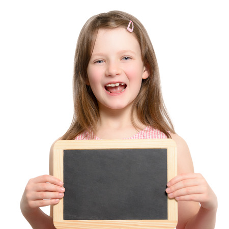 Excited little girl calling out for attention with her mouth open holding a blank slate or chalkboard with copy space for your text photo