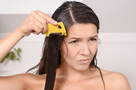 piojos: Mujer pein�ndose los piojos en el pelo con un peine de piojos muecas mientras saca los dientes finos a trav�s de sus largas trenzas marrones para controlar la infestaci�n contagiosa de peque�os insectos sin alas