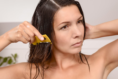 tresses: Woman combing out lice in her hair with a lice comb grimacing as she pulls the fine teeth through her long brown tresses to control the contagious infestation of tiny wingless insects