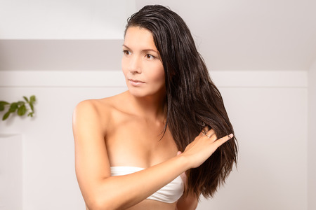 sensuous: Young woman in lingerie wearing a strapless white bra standing in the bathroom styling her long hair with her fingers after showering in the morning