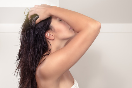 Attractive serious young woman standing in her bathroom with bare shoulders shampooing her long brown hair massaging her scalp with her fingers photo