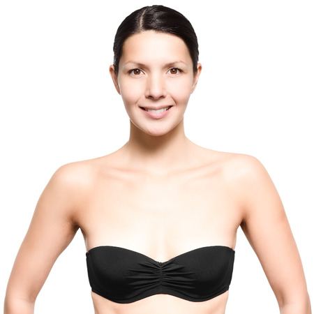 unemotional: Attractive slim young woman wearing a black strapless bra standing looking directly at the camera with a smile, isolated on white Stock Photo
