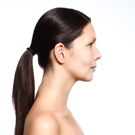 hair tied: Head and shoulders portrait of a young woman with a serious expression standing in profile with her long brown hair neatly tied in a pony tail revealing her graceful long neck isolated on white