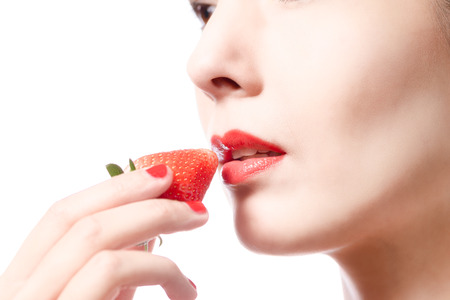 Beautiful woman with sensual red lips eating a luscious ripe red fresh strawberry with her lips parted in anticipation of the treat, close up partial view of her face isolated on white