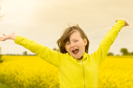 Pretty little girl rejoicing in the countryside laughing with her arms spread wide in her yellow top matching the colorful yellow rapeseed flowers in the field behind her photo