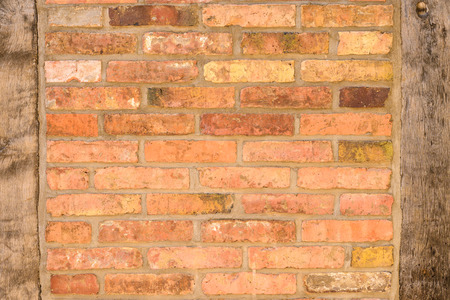 uprights: Old brick wall background texture with wooden uprights on either side constructed of old thin clay face bricks Stock Photo
