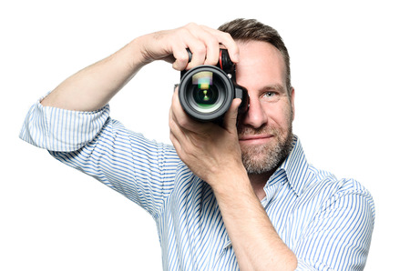 Male photographer focusing and composing an image with his professional digital Dslr camera pointing the lens directly at the viewer, upper body isolated on white photo