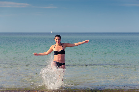 frolicking: Happy attractive young woman in a bikini frolicking on a tropical beach having fun laughing and kicking up spray from the sea with her foot, with copy space to the right