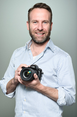Handsome photographer with a friendly smile standing holding his camera laughing at the camera, upper body portrait in relaxed pose on grey