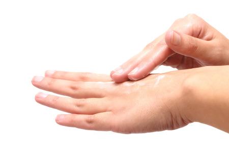 Close-up der weiblichen Händen, während die Anwendung Feuchtigkeitslotion, um beschädigte und trockene Haut zu reparieren, auf grauem Hintergrund Standard-Bild