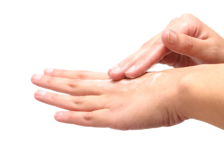 Close-up of female hands while applying moisturizing lotion in order to repair damaged and dry skin, on grey background Stock Photo