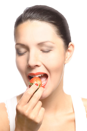 tantalizing: Beautiful woman with sensual red lips eating a luscious ripe red fresh strawberry with her lips parted in anticipation of the treat, close up view of her face isolated on white