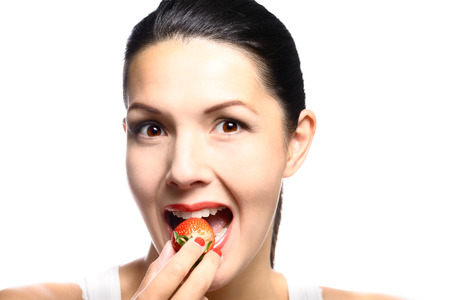 luscious: Beautiful woman with sensual red lips eating a luscious ripe red fresh strawberry with her lips parted in anticipation of the treat, close up view of her face isolated on white