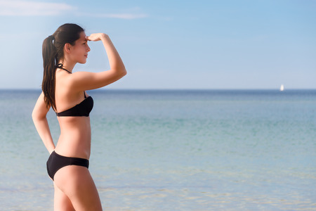 Sexy shapely young woman in a black bikini standing sideways with her hand raised to her forehead looking out over the ocean with copyspace photo