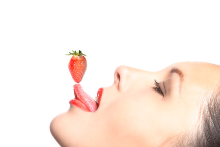 sensuous: Side view of beautiful woman balancing a strawberry on the tip of her tongue. Stock Photo
