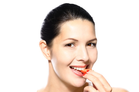 tantalizing: Beautiful woman with sensual red lips eating a luscious ripe red fresh strawberry with her lips parted in anticipation of the treat, close up partial view of her face isolated on white
