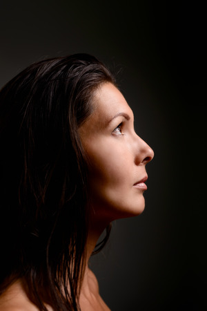 longing: Profile view of a beautiful serious serene young woman standing in shadows staring up into the light with a look of longing and loneliness Stock Photo