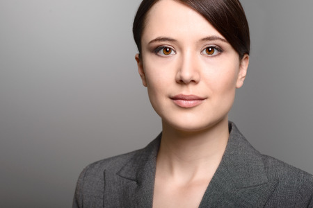 inscrutable: Attractive stylish young businesswoman with an attentive expression looking directly at the camera, closeup of her face on a grey background with copy space