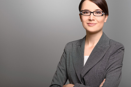Stylish young businesswoman with a friendly expression wearing glasses looking directly at the camera, closeup of her face on a grey background with copy space photo