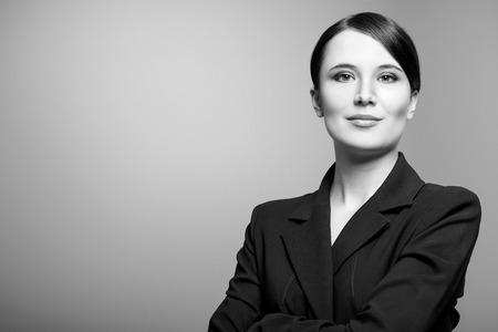 enigmatic: Bianco e nero, ritratto di una bella donna elegante professionale in piedi con le braccia piegate in una giacca elegante guardando la telecamera con un sorriso enigmatico, con copia spazio Archivio Fotografico