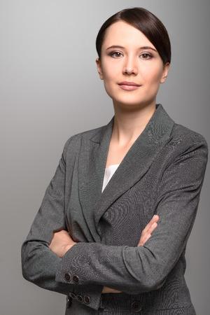 직접 카메라를 찾고 세심한 표정으로 매력적인 세련된 젊은 사업가, 복사 공간이 회색 배경에 그녀의 얼굴의 근접 촬영