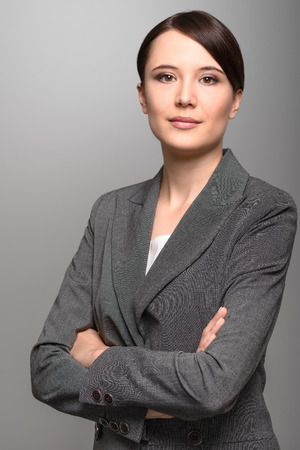 Attractive stylish young businesswoman with an attentive expression looking directly at the camera, closeup of her face on a grey background with copy space