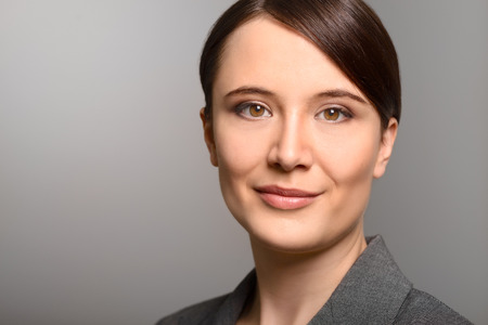 inscrutable: Stylish young businesswoman with a friendly expression looking directly at the camera, closeup of her face on a grey background with copy space