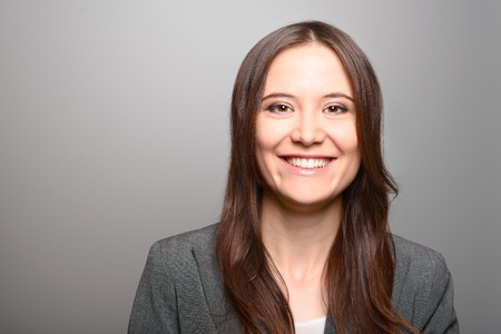 vivacious: Attractive stylish young professional woman with a lovely vivacious smile looking directly at the camera, head and showith a lovely vivacious smile looking directly at the camera, head and shoulders on grey with copy space Stock Photo