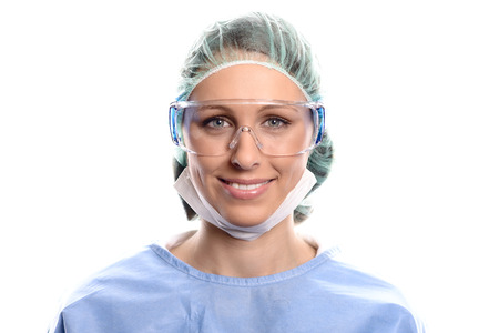 Young female nurse or doctor in surgical scrubs wearing a theatre gown, mask, goggles and a cap looking directly at the camera, head and shoulders isolated on white